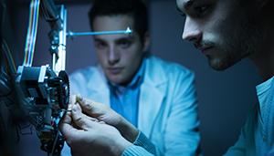 Photo de deux ingénieurs autour d'une imprimante 3D